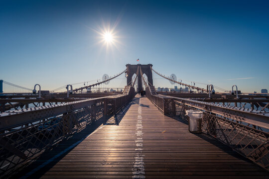 Famous Brooklyn bridge over river against clear blue sky with bright sun in New York City