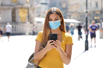 Travel concept. Beautiful young traveler woman with protective mask using application map on smart phone. Tourist girl exploring city with mobile phone.