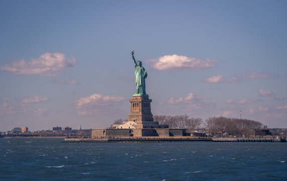 Magnificent view of colossal Statue of Liberty located on Liberty Island in New York against blue cloudy sky in spring day