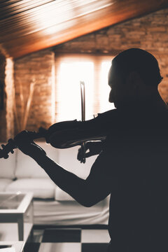Side view of silhouette of male musician playing violin and looking at music sheets while practicing in living room