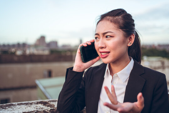 Side view of young Asian business lady in formal outfit talking on smartphone while working remotely on rooftop terrace in city