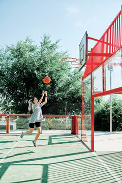 Full body side view of young sporty woman performing jump shot while playing basketball alone on sports ground
