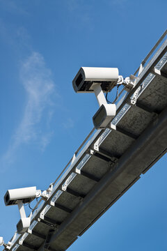 From below of road security camera recording speed of automobile driving along highway on sunny day with blue sky