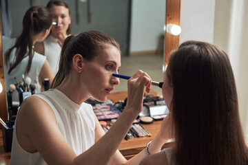 Positive young female makeup artist applying powder on clients face by using brush against cozy big mirror with lights in contemporary beauty salon