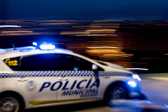 Contemporary police vehicle on motion with siren light on the road on background of amazing night cityscape