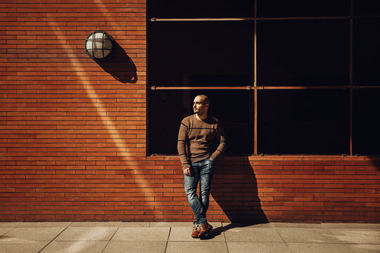 Full body confident young bald male in casual jumper and jeans looking away while standing against brick building on street