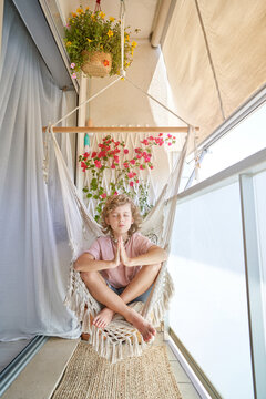 Calm barefoot child with closed eyes in casual wear sitting in hammock with crossed legs and prayer hands above wicker carpet on balcony with potted plant in daylight