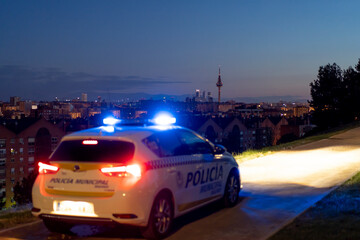 Contemporary police vehicle with siren light on the road on background of amazing night cityscape Fotomurales