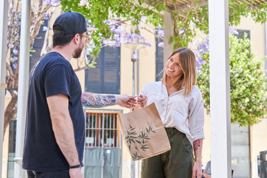 Side view of male server passing paper bag with takeaway food to charming trendy woman on street in summertime