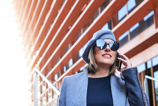 Low angle of well dressed female entrepreneur standing along futuristic building and discussing business issues on smartphone while looking away with sunglasses