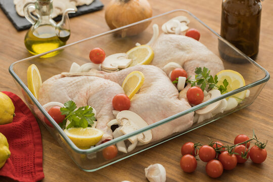 Uncooked chicken with tomatoes lemon and mushrooms in glass oven recipient resting on a wooden table