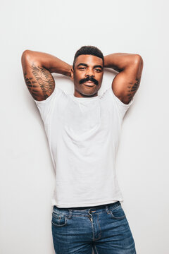 Serious black man with casual outfit posing over white background looking at camera