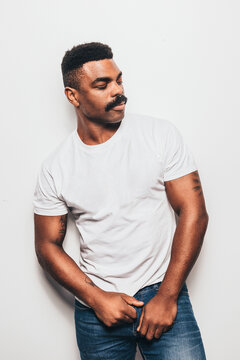 Serious black man with casual outfit posing over white background looking away