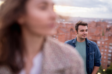 Calm and content man with brown hair walking and looking away being in love with blurred woman on foreground Wall mural