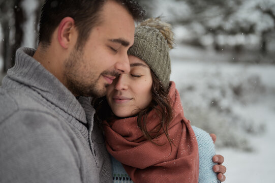 Casual man and woman in warm hat standing with eyes closed against coniferous trees in winter time