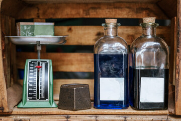 Natural soap bar placed on vintage metal balance scale near glass bottle with cosmetic product on wooden shelf in eco friendly shop