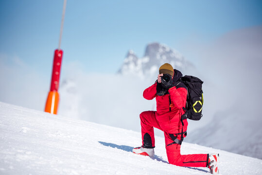 Unrecognizable in red warm outfit and ski boots and with backpack taking photos looking at camera with professional equipment on mountain slope in sunlight