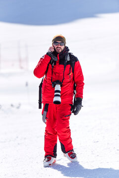 Man in red warm outfit and ski boots and with backpack taking photos with professional equipment on mountain slope in sunlight looking at camera