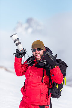Cheerful man in red warm outfit and ski boots and with backpack taking photos with professional equipment on mountain slope in sunlight looking at camera