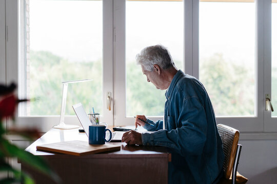 Senior man using calculator and laptop at home