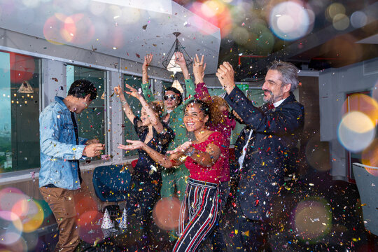 LGBT party(lesbian, gay, bisexual, transgender)with motion blurred, Successful diverse team celebrating at workplace. Group of cheerful multiethnic businesspeople. Concept of Pride Month nightlife