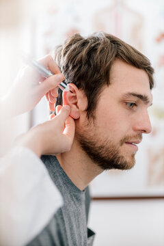 Female alternative practitioner giving man acupuncture with akupen in ear