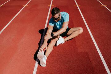 Male athlete stretching on tartan track