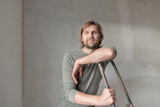 Confident man leaning on ladder during renovation
