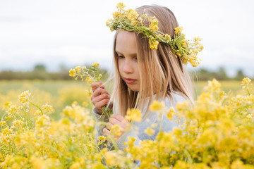 Portrait of girl with wreath of rape flowers