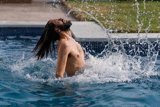 Bearded man in swimming pool splashing with water