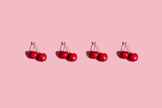 Row of fresh cherries on pink background