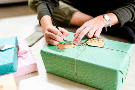 Woman's hands writing on present tag