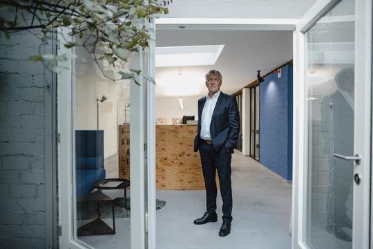 Senior businessman standing in open office door with hands in pockets