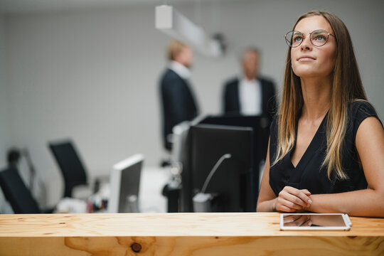Businesswoman standing in office, leaning on wooden counter, looking up