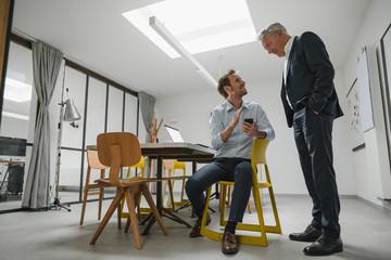 Senior businessman listening to younger business partner, holding smartphone
