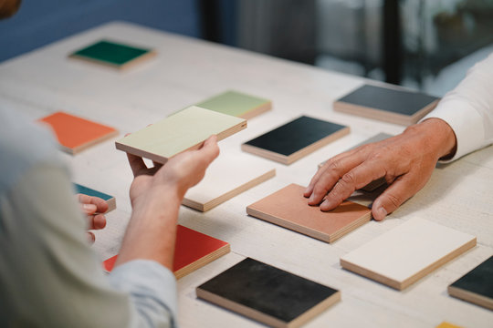 Hands of architects choosing colour samples in office