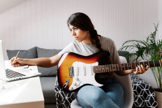 Young woman writing while using laptop and electric guitar at home