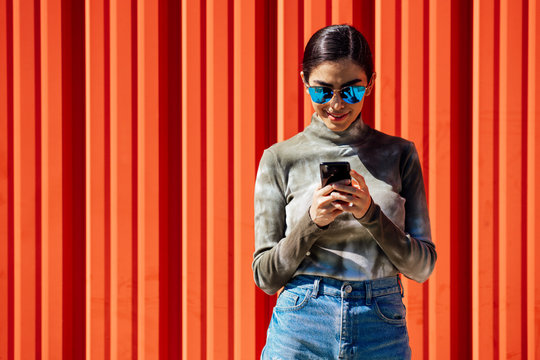 Smiling young woman using smart phone while standing against red corrugated wall on sunny day