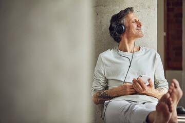 Senior man with headphones listening music in a loft flat