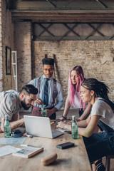 Creative team having business meeting in loft office using laptop