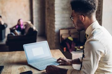 Creative businessman using laptop in loft office