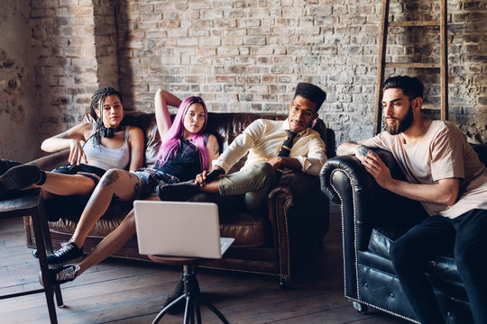 Group of friends sitting on sofa in a loft looking at laptop