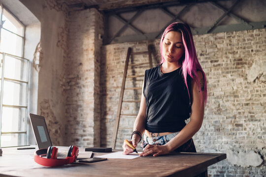 Creative businesswoman with pink hair working at table in loft office