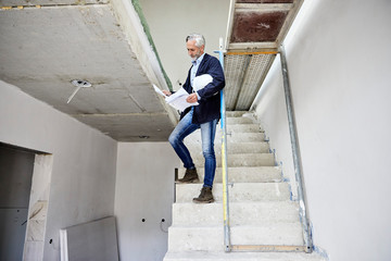 Architect holding building plan on a construction site
