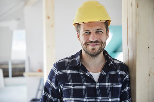 Portrait of a smilling worker wearing hard hat on a construction site