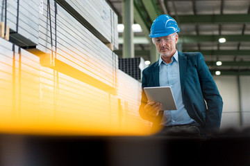 Mature businessman wearing hard hat and safety goggles in a factory using tablet