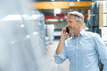 Smiling mature businessman on the phone in a factory