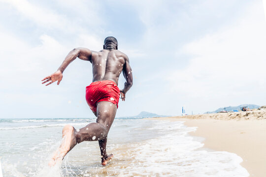 Rear view of athletic man running on beach