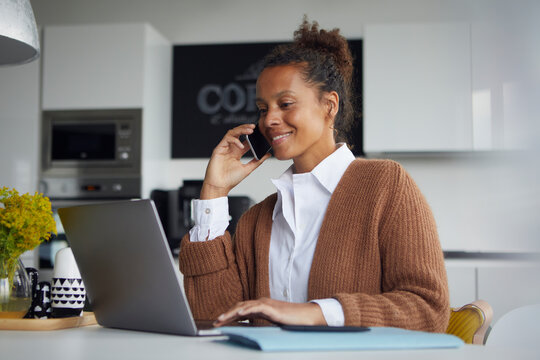 Smiling businesswoman on the phone sitting in kitchen working on laptop