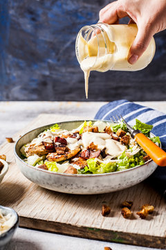 Hand of person pouring dressing over bowl of Caesar salad with romaine lettuce, ParmesanÔøΩcheese, bacon, chicken breast and croutons